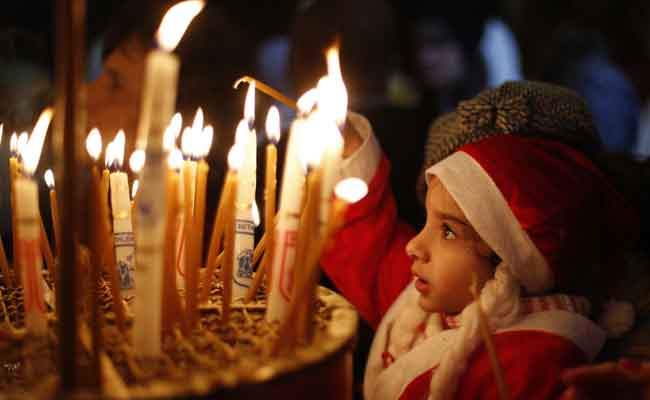 child with christmas candle